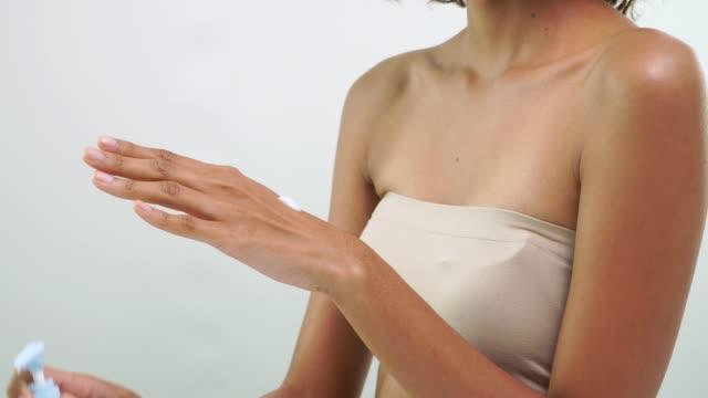 vidéos et rushes de gros plan de main de femme africaine frottant la peau avec le produit de soin de peau beauté sur fond blanc. - marchandise