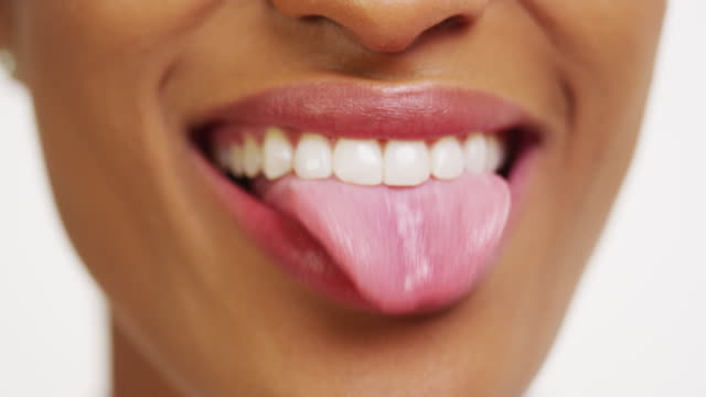 vídeos y material grabado en eventos de stock de close up of african woman with white teeth smiling and sticking tongue out - dientes humanos
