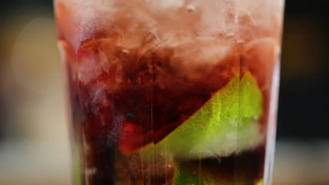 close up of alcoholic cocktail drink with ice and lime in it on the bar counter ready to drink - aperitivo video stock e b–roll