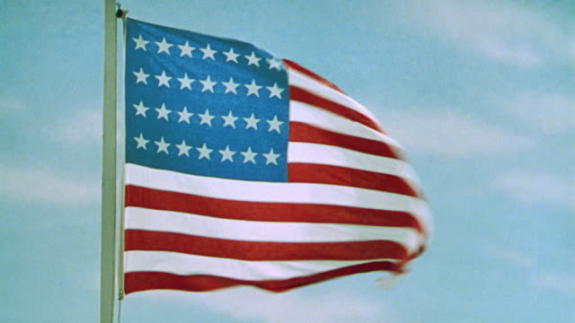 vidéos et rushes de close up of american flag with 28 stars blowing in wind / blue sky in background / the flag speaks - drapeau