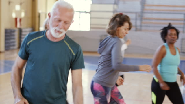 close up of an active senior man dancing in gym - anziani attivi video stock e b–roll
