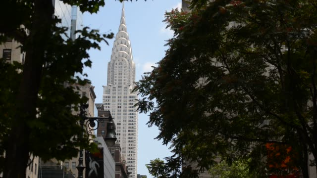 vídeos de stock e filmes b-roll de close up of an american flag waving over the streets of new york city with the top of the chrysler building slowly revealed behind it close up shot... - prédio chrysler