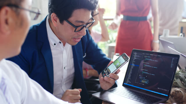 close up of an app developer demoing his social media app on a mobile phone and explaining it to a colleague - computer programmer stock videos & royalty-free footage