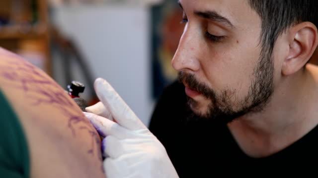 close up of an artist making tattoo on male customer - giuntura umana video stock e b–roll