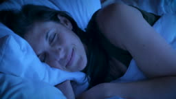 Close up of an attractive woman smiling while sleeping at night