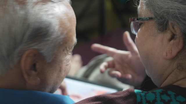 a close up of an elder couple discussing and using a touch screen tablet in a positive outlook - over the shoulder stock videos & royalty-free footage