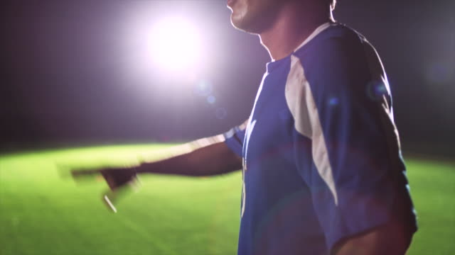 slo mo. cu. close up of an exhausted sweaty soccer player holding up his hand and then running off for a goal kick on a soccer field during a nighttime match - defender soccer player stock videos and b-roll footage