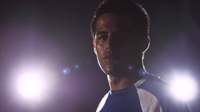 CU. Close up of an exhausted sweaty soccer player standing on a soccer field during a nighttime match and looks at camera