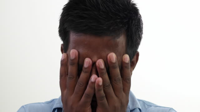Close up of an Indian man, distraught and sad, looking straight at the camera