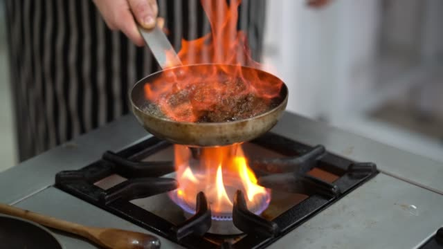 close up of an unrecognizable chef doing a flambé technique on a piece of steak - argentina stock videos and b-roll footage