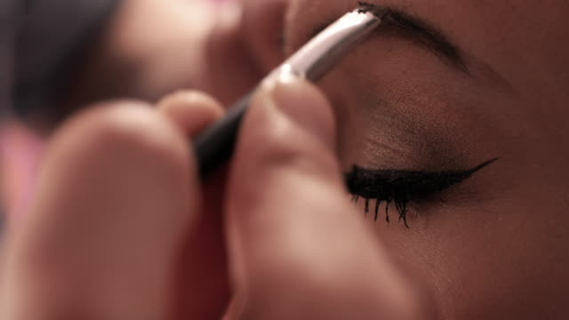 Close up of applying make-up on woman's eyebrow.