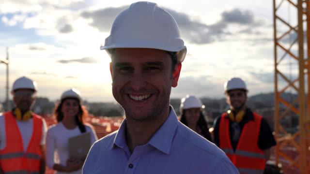 Close-up de líder arquiteto olhando para câmera sorrindo com braços cruzados e sua equipe esperando no fundo em uma construção