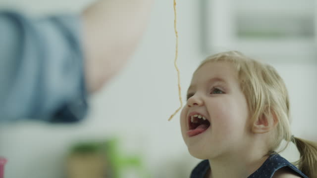 close up of arm of mother feeding long spaghetti to smiling baby daughter / lehi, utah, united states - pulling funny faces stock videos & royalty-free footage