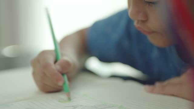vidéos et rushes de fermez-vous vers le haut des garçons asiatiques dessinent et colorient dans leurs livres pendant l'école à la maison tandis que l'école est fermée en raison de l'épidémie de covid-19. - élève du primaire
