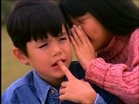 close up of Asian girl whispering to Asian boy / smiling / Connecticut