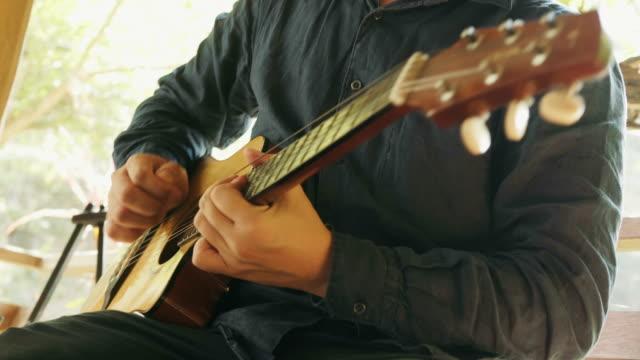 vídeos de stock, filmes e b-roll de close-up do homem asiático está tocando guitarra no terraço para atividade de relaxamento - violão acústico