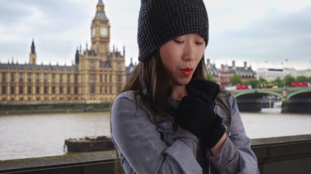 close up of asian millennial wearing beanie and mittens near big ben in london - big ben点の映像素材/bロール