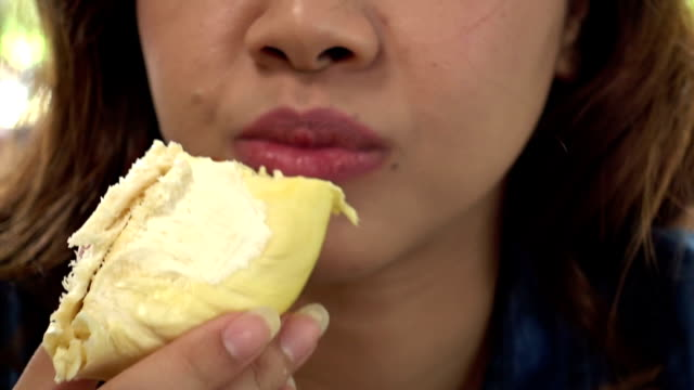 Close up of asian woman eating durian