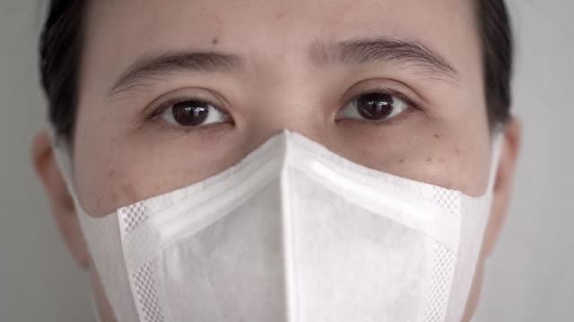 vídeos de stock e filmes b-roll de close up of asian women eyes with hygienic mask or medical face mask looking at camera - estado médico