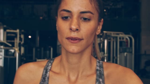 close up of athletic young woman focusing while working out on elliptical machine - cross trainer stock videos & royalty-free footage