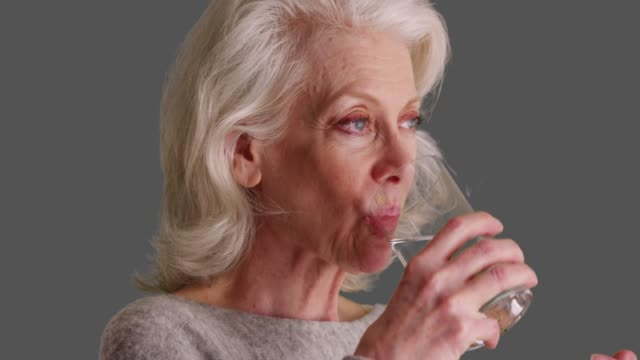 vidéos et rushes de close up of attractive elder woman swallowing pill with water on grey background - comprimés