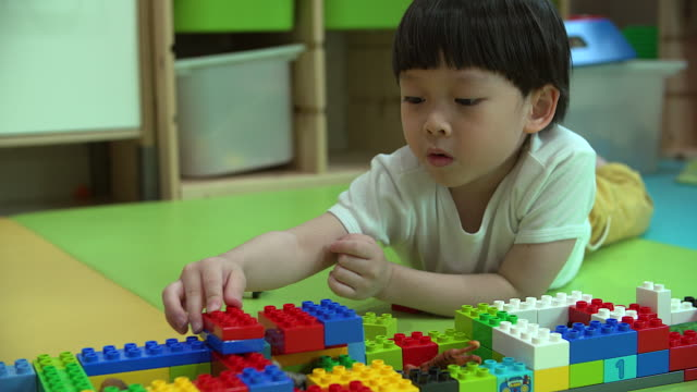 close up of baby boy playing with colorful plastic bricks. - block shape stock videos & royalty-free footage