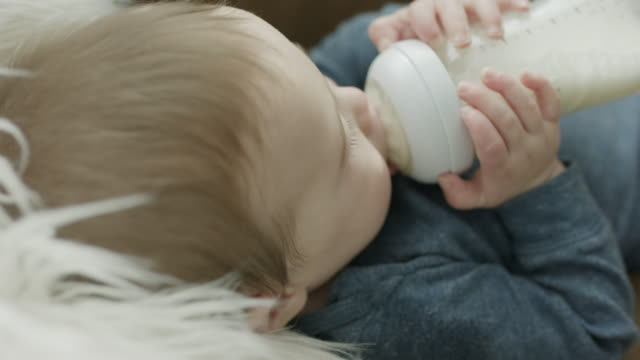 stockvideo's en b-roll-footage met close up of baby drinking from baby bottle / provo, utah, united states - zuigfles