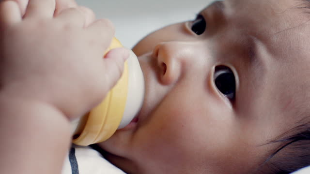 close up of baby drinking from baby bottle - milk bottle stock videos & royalty-free footage
