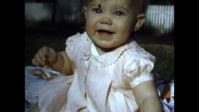 close up of baby in pink dress sitting on picnic blanket smiling at the camera, she is eating grass; baby crawling and laughing; white fence and... - only girls stock videos & royalty-free footage