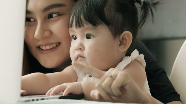 close up of baby touching computer with mother. - affectionate stock videos & royalty-free footage