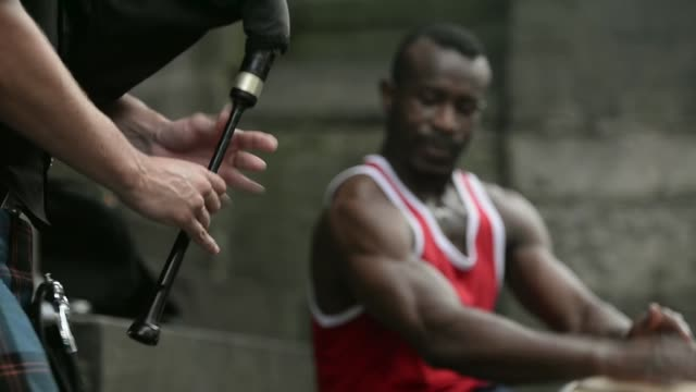 close up of bagpiper's hands as he performs with an african drummer. street entertainers perform on edinburgh's royal mile during the city's festival... - kilt stock videos & royalty-free footage