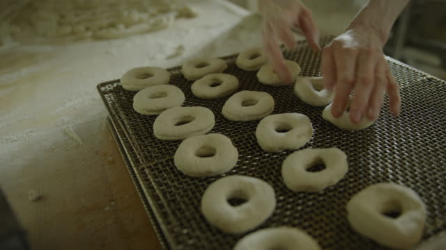 close up of baker placing donut dough on baking rack / pleasant grove, utah, united states - dough stock videos & royalty-free footage