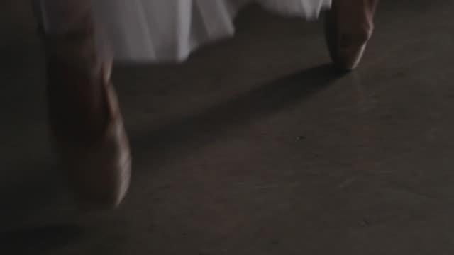 Close up of ballerina's point shoes performing assemblés and deboulé