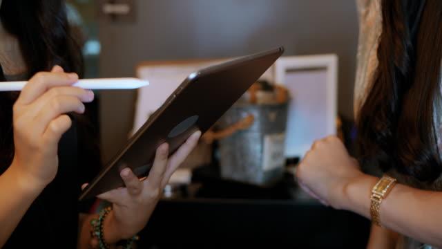 デジタルタブレットを使用して注文を取るバリスタのクローズアップ。 - 外食産業関係の職業点の映像素材/bロール