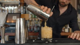 Close Up Of Barman Pouring Cocktail Into Glass