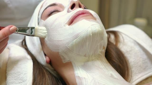 vídeos de stock, filmes e b-roll de close-up da mão de esteticista, aplicação de máscara facial com um pincel - tratamento de beleza evento