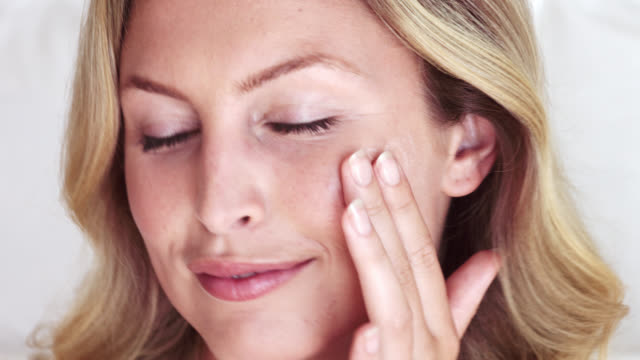close up of beautiful blonde woman applying a face cream. - applying stock videos & royalty-free footage