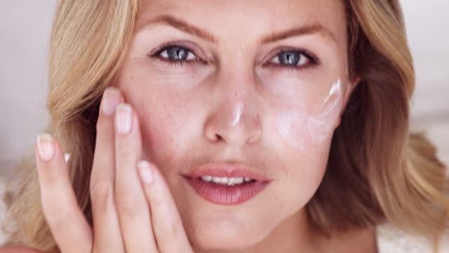 Close up of beautiful blonde woman applying moisturiser to face.