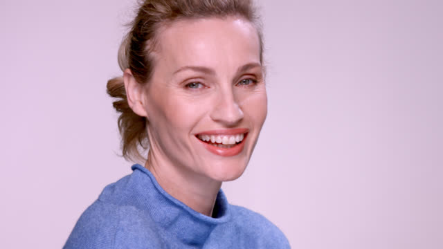 close up of beautiful blonde woman wearing a blue jumper. - anti aging stock videos & royalty-free footage