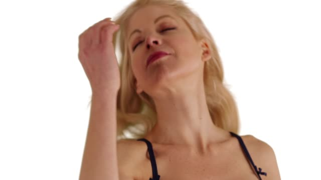 vidéos et rushes de close up of beautiful caucasian woman letting down her hair on white background - queue de cheval