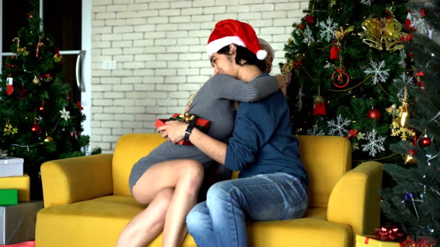 close up of beautiful female surprise her boyfriend by giving a gift and hugging togetherness in christmas day - tree hugging stock videos & royalty-free footage