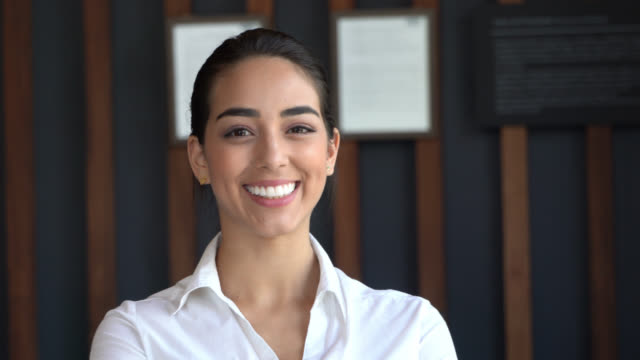 vídeos de stock e filmes b-roll de close up of beautiful latin american hotel receptionist facing camera smiling - hotel