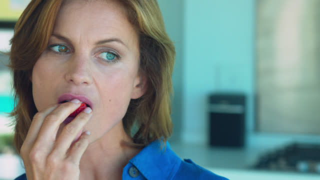 close up of beautiful mature woman eating a strawberry. - fruit bowl stock videos & royalty-free footage