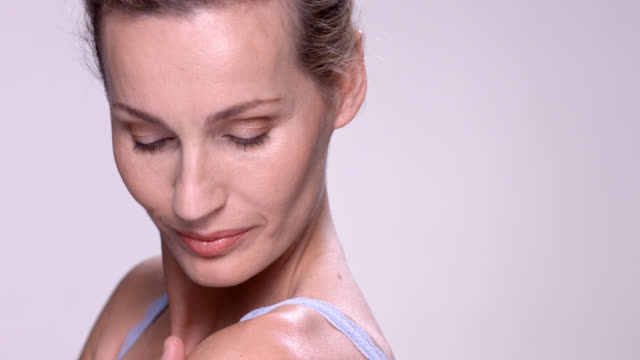 vídeos de stock, filmes e b-roll de close up of beautiful mature woman gently rubbing her arm. - tratamento de pele