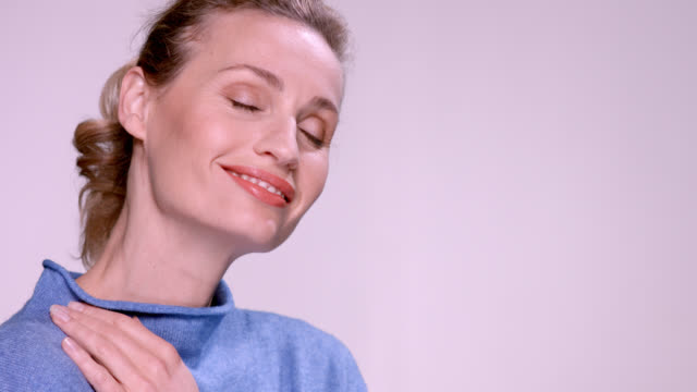 close up of beautiful mature woman in a blue jumper. - hair back stock videos & royalty-free footage