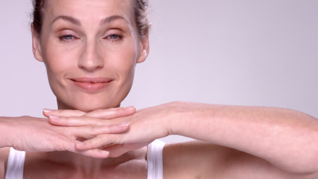 close up of beautiful mature woman resting her chin on her hands. - one mature woman only stock videos & royalty-free footage