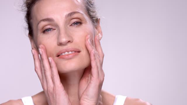 close up of beautiful mature woman running her fingers over her face. - skönhet och kroppsvård bildbanksvideor och videomaterial från bakom kulisserna