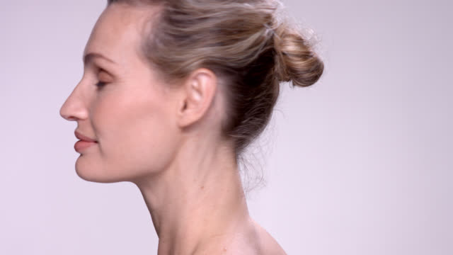 close up of beautiful mature woman with glowing skin. - hair bun stock videos and b-roll footage