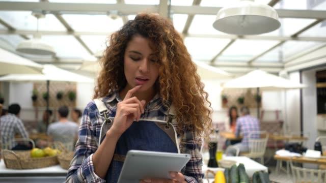vídeos de stock e filmes b-roll de close up of beautiful waitress putting an order from a customer on the system using a digital tablet - empregada de mesa