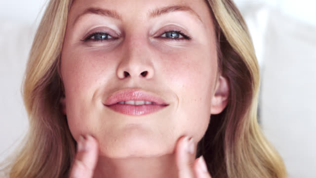 close up of beautiful woman gently rubbing her face after applying moisturiser. - face cream stock videos and b-roll footage